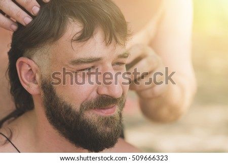Young handsome bearded man at the time of hair cutting through the clipper, sunny