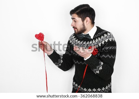Young handsome bearded man in a knitted sweater with a decor in the form of hearts shows the situation alone on Valentine's Day - stock photo