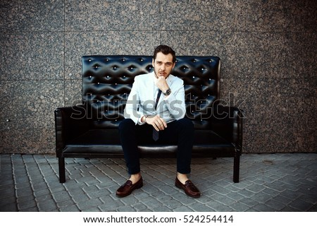 Young handsome bearded stylish man sitting on comfortable leather sofa outdoors