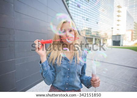 Young handsome blonde caucasian girl having fun playing with soap bubble in the city wearing jeans shirt and floral skirt - emancipation, carefreeness, youth concept - stock photo