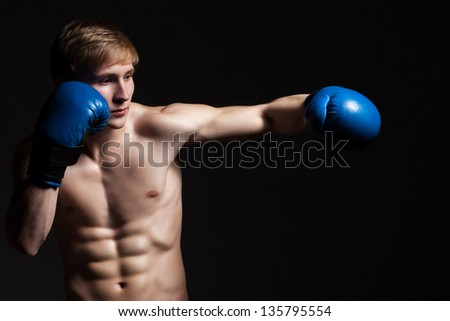 Young handsome boxer in a movement over dark background