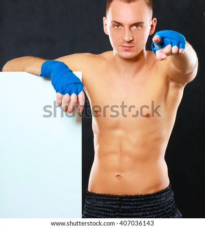 Young handsome boxer man standing near board and pointing at you, isolated on black background
