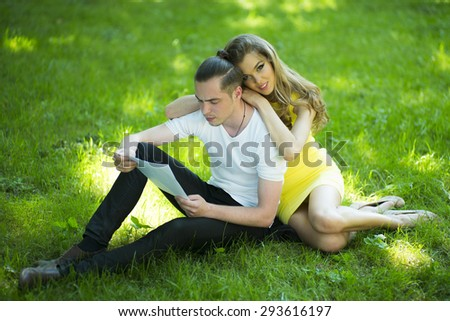 Young handsome boy relaxing in park sitting with pretty girl on green grass reading on natural background, horizontal picture