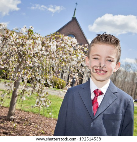 Young handsome boy standing outside a church - stock photo