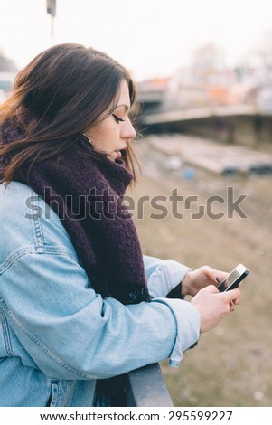 Young handsome brunette caucasian girl using a smartphone connected online in a park in the city. technology, connectivity, e-commerce- business, social network concepts