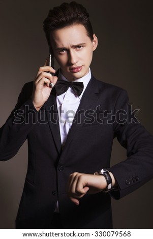 Young handsome brunette macho businessman in black suit and white shirt with bow tie talking on a phone looking on his watch. neutral background