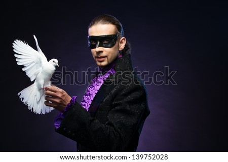 Young handsome brunette magician man in stage costume with his trained white dove - stock photo