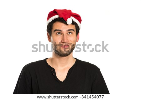 Young handsome brunette man wearing red hut, black t-shirt,  smiling, happy, on white background with copy space, looking up, making funny face expression