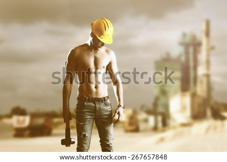Young handsome builder man with big hammer - stock photo