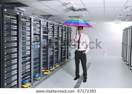 young handsome business man  engineer in  businessman hold  rainbow colored umbrella in server datacenter room  and representing security and antivirus sofware protection concept - stock photo