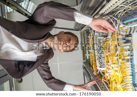 young handsome business man engineer in data center server room inside cabinet bottom view