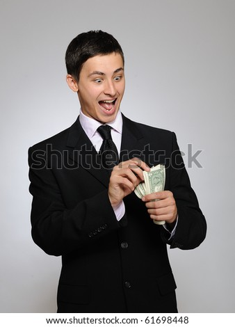Young handsome business man in black suit and tie counting money. gray background