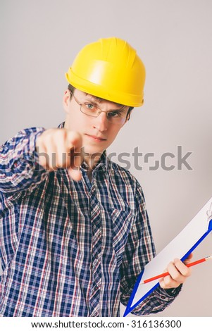 young handsome business man in yellow builder's helmet with blueprint pointing on something
