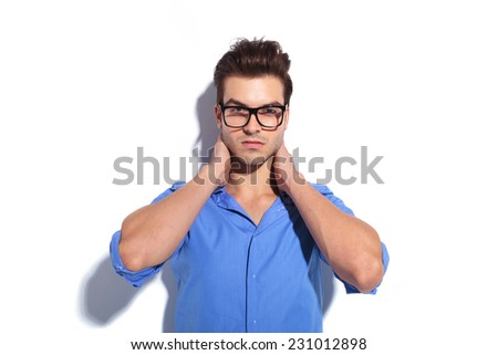 Young handsome business man leaning on a white wall while holding both hands to his neck. - stock photo