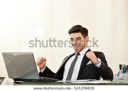Young handsome business man smiling and celebrating an achievement with his arms risen and his fists clenched, at his desk, looking at laptop - stock photo