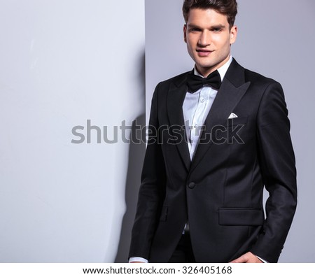 Young handsome business man stading on studio background.