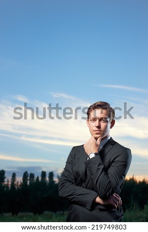 Young handsome business man thinking at the sky background