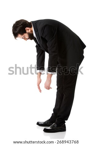Young handsome businessman bending down. - stock photo