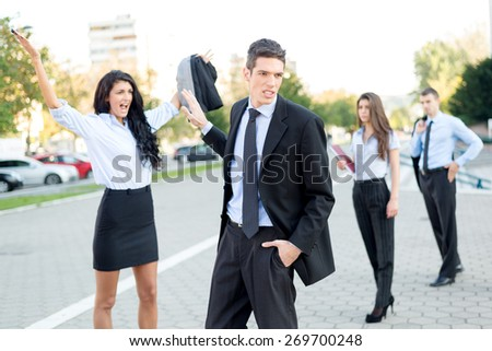 Young handsome businessman dressed elegantly indifferent waved his hand toward a young attractive businesswoman who yelling at him on the street in front of colleagues who viewed their fight. - stock photo