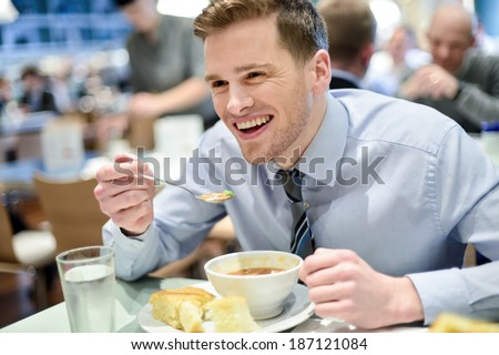 Young handsome businessman eating lunch in a cafe - stock photo