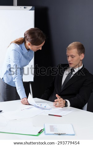 Young handsome businessman explaining his female colleague new idea - stock photo