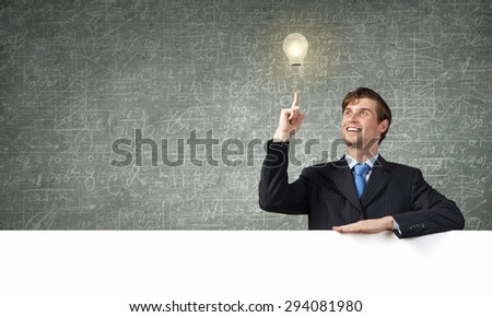 Young handsome businessman holding white blank banner