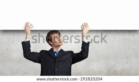Young handsome businessman holding white blank banner above head