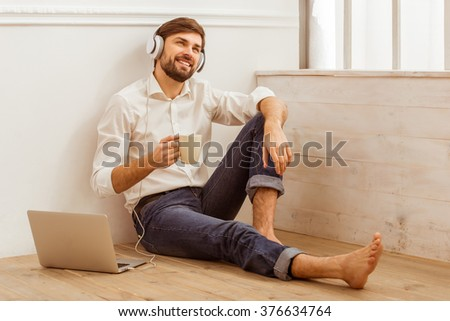 Young handsome businessman in white classical shirt and jeans using a laptop, listening to music, holding a cup and smiling while sitting on the wooden floor - stock photo