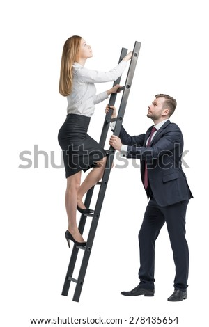 Young handsome businessman is holding a ladder for the lady in a formal clothes to boost her ideas. The concept of the success and team working - stock photo
