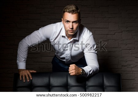 Young handsome businessman relies on leather couch in confident pose