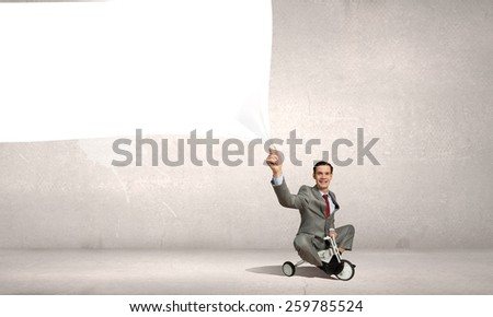 Young handsome businessman riding three wheeled bicycle - stock photo