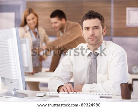 Young handsome businessman sitting at desk at further education training.? - stock photo