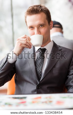 Young handsome businessman sitting in a cafe drinking coffee - stock photo