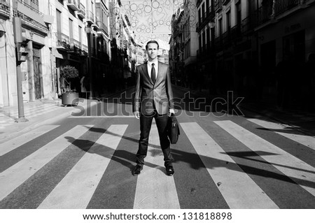 Young handsome businessman sitting in a crosswalk - stock photo