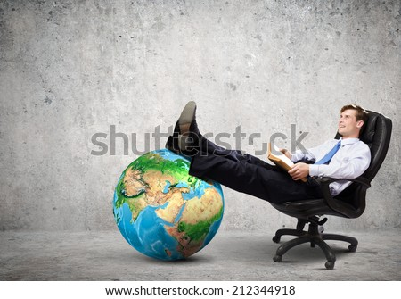 Young handsome businessman sitting in chair with book in hands. Elements of this image are furnished by NASA - stock photo