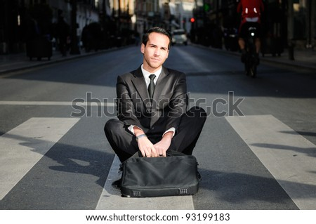 Young handsome businessman sitting in the street - stock photo