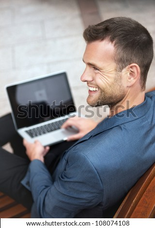 Young handsome businessman sitting on a wooden bench in the city with a laptop and smiling. From above - stock photo