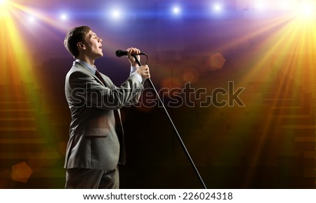 Young handsome businessman standing on stage with microphone