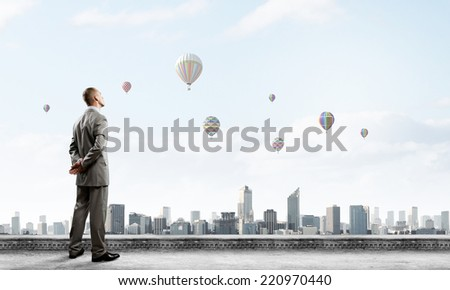 Young handsome businessman standing on top of building - stock photo