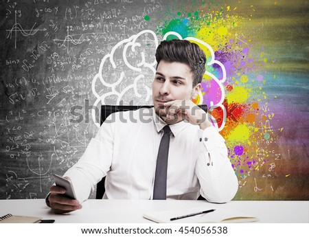 Young handsome businessman thinking about something sitting in front of wall with sketch of brain on it. Concept of thinking - stock photo