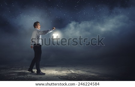 Young handsome businessman walking in darkness with lantern - stock photo