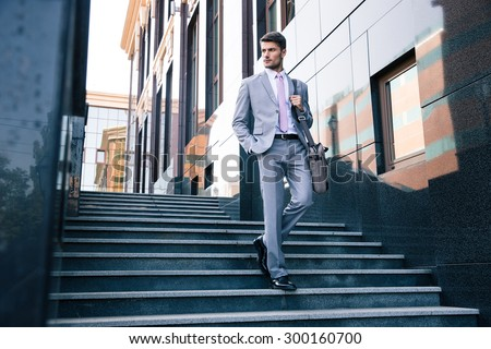 Young handsome businessman walking on stairs outdoors - stock photo