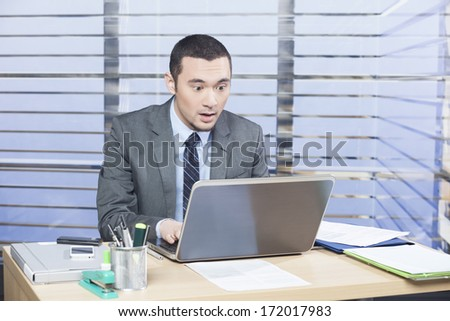 Young handsome businessman watching notebook - surprised with the information displayed on the scree - expression