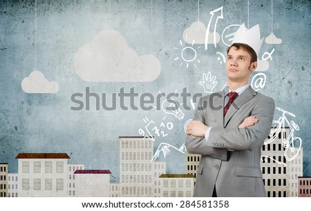 Young handsome businessman wearing white paper crown