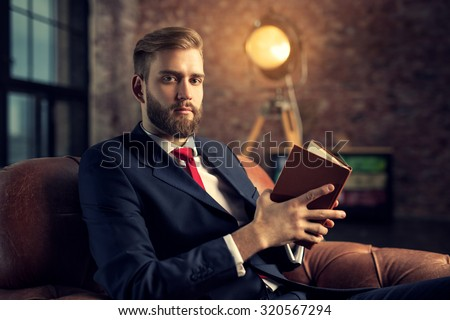 Young handsome businessman with beard in black suit sitting on chair reading book. - stock photo