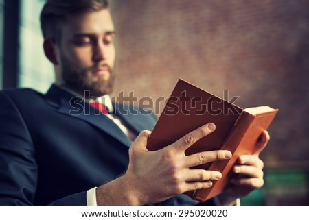 Young handsome businessman with beard reading book. Focus on hands and book.