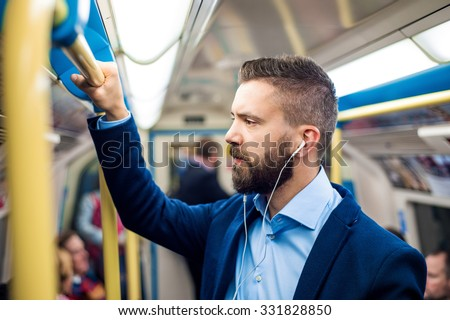 Young handsome businessman with smartphone in subway - stock photo