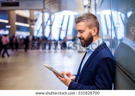 Young handsome businessman with tablet in subway - stock photo