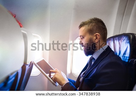 Young handsome businessman with tablet sitting inside an airplane - stock photo