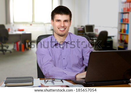 Young handsome businessman working on laptop in bright office.
